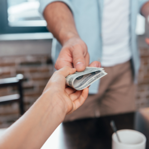 Business owner accepting payment after starting a business that actually makes money